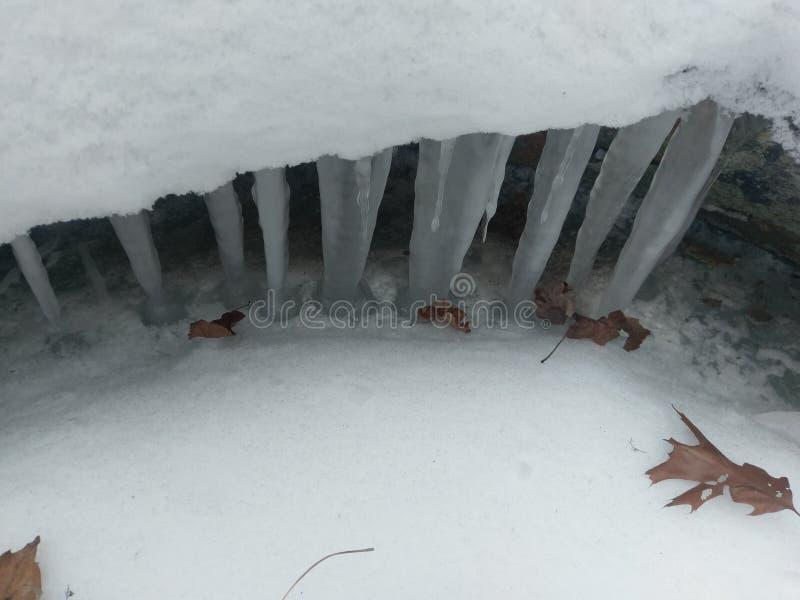 Istappar som hänger ner från snöavsatsen ovanför ström arkivbild
