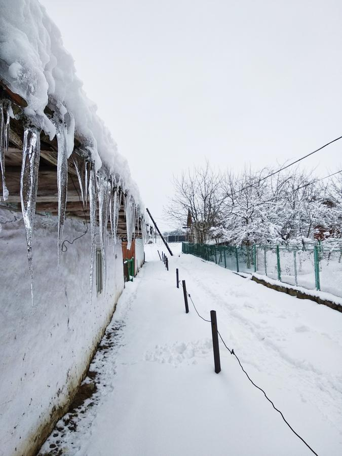 Istappar som hänger på taket av det gamla huset, jord täckas med snö, vandringsled på snö Vinter i ukrainsk by arkivfoton