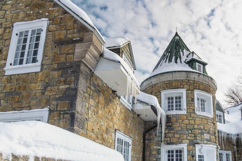 Istappar som hänger på taket av huset royaltyfri foto
