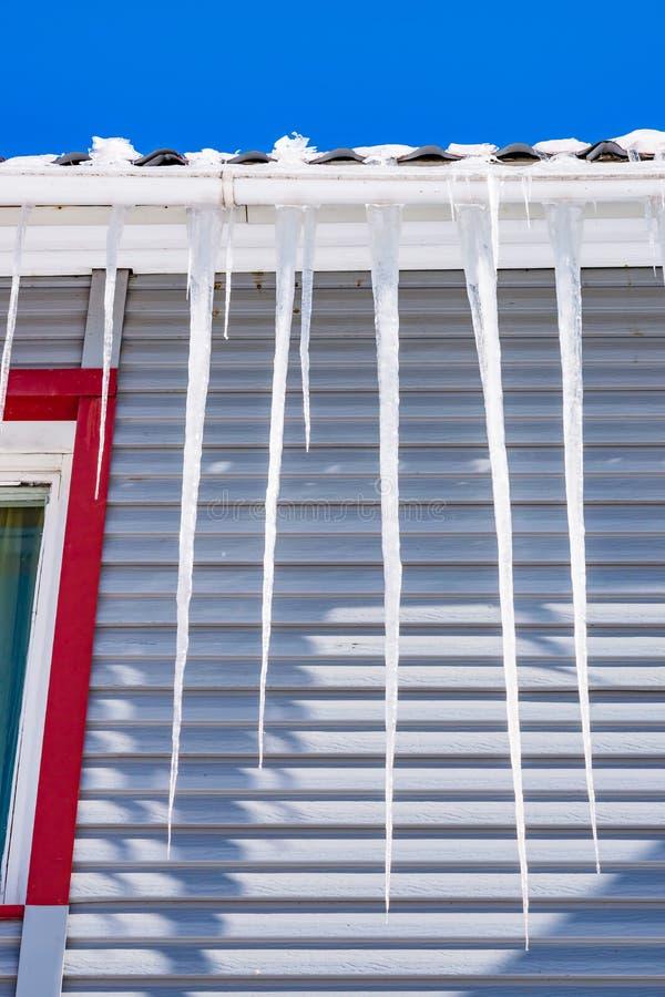 Istappar som på våren hänger från taket av huset under solnedgången, begreppet av säsongsbetonade faror, arkivfoton