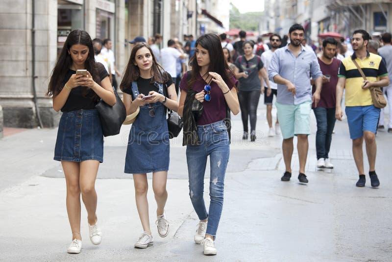 Istiklal的人们 简而言之步行沿着向下街道的女学生 免版税库存照片