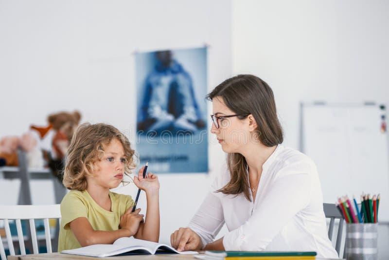 Istitutore che ha una lezione con un bambino distratto con le edizioni di concentrazione fotografie stock libere da diritti