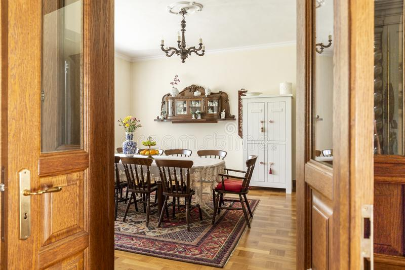Istna fotografia antykwarski jadalni wnętrze z dużym stołem, krzesłami, ścienną spiżarnią i dywanem, Widok przez drzwi obraz royalty free