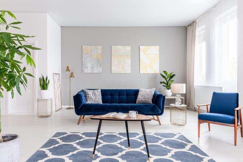 Istna fotografia elegancki żywy izbowy wnętrze z błękitną kanapą, zdjęcie stock
