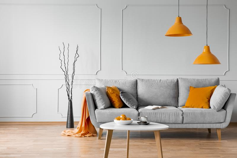 Istna fotografia prosty żywy izbowy wnętrze z pomarańczowymi lampami, poduszkami i popielatą kanapą, obraz stock