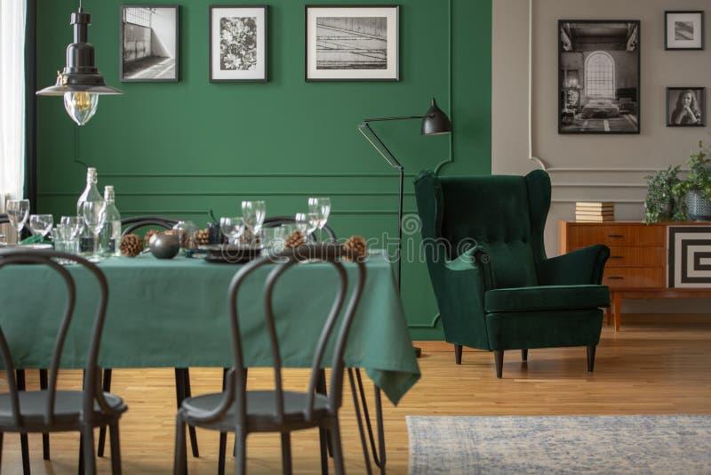 Istna fotografia stół z zielonymi krzesłami w zamazanym przedpolu i comfy karło w tle w łomotać płótna i czerni obrazy royalty free