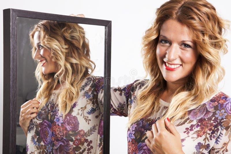 Istna młoda kobieta patrzeje w lustrze obraz stock