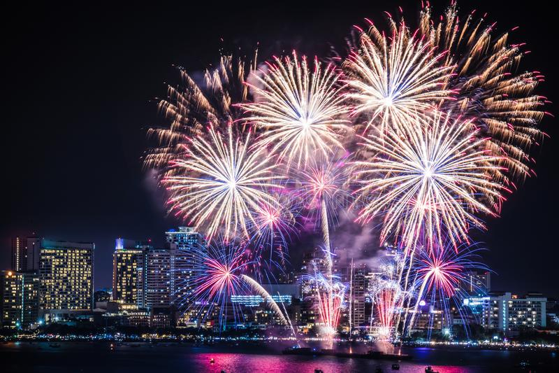 Istny fajerwerku festiwal w niebie dla świętowania przy nocą z miasto widokiem przy tłem i łódkowatego unosić się na morzu zdjęcie stock