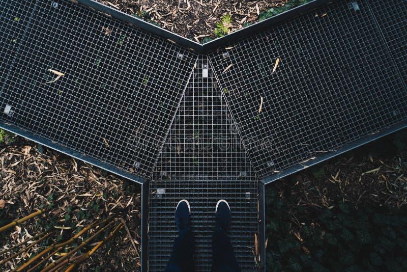 Istota ludzka cieki stoi na metalu zwężają się droga przemian w ogródzie botanicznym obraz stock