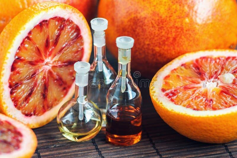 Istotni oleje w szklanej butelce z świeżą, soczystą, dojrzałą, czerwoną pomarańcze, kąpielowy piękna składu olej mydli traktowani obraz royalty free