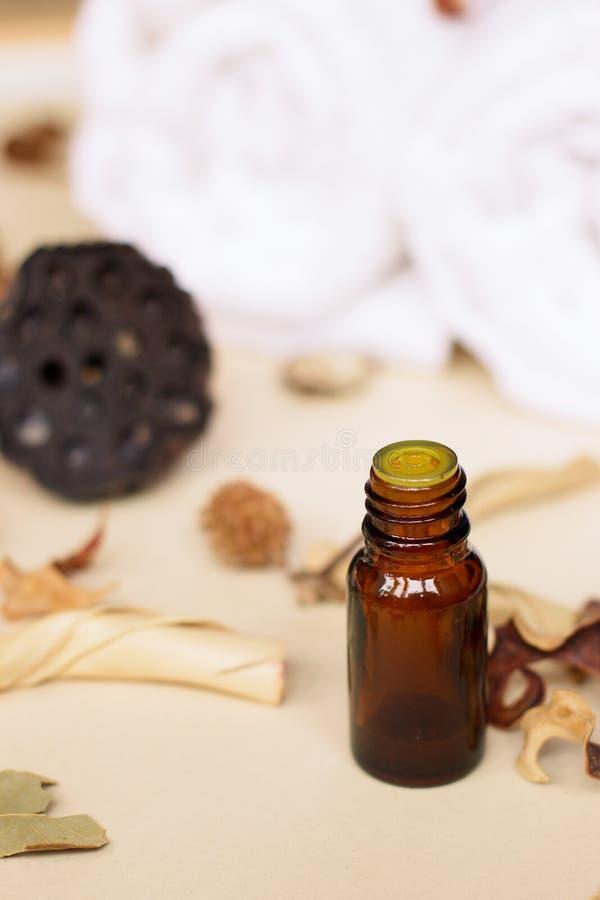 Istotny olej i suszy kwiaty na beżowym tle fotografia stock
