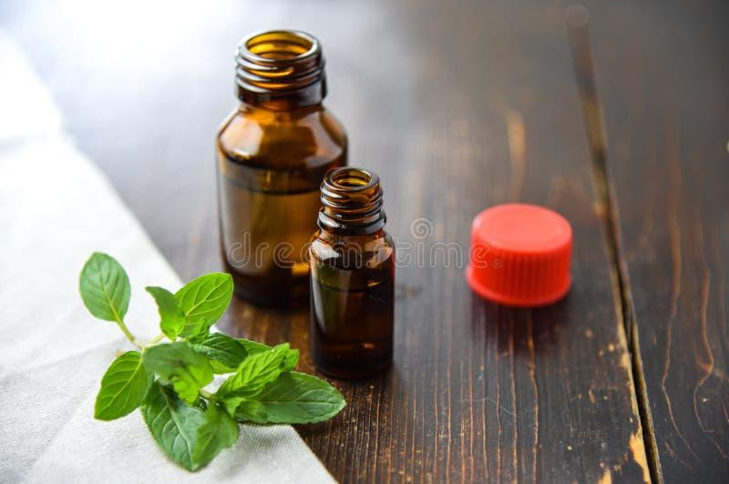 Istotny olej miętówka w małej brown butelce z świeżą zieleni mennicą na starym drewnianym tle, selekcyjna ostrość obrazy royalty free