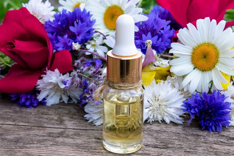 Istotny olej w szklanej butelce blisko wildflowers na drewnianym tle zdjęcia stock