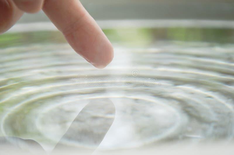 istoty ludzkiej palcowy macanie na wody powierzchni zdjęcia stock