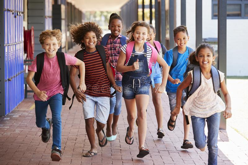 Istruisca i bambini che si dirigono nel corridoio della scuola elementare, vista frontale fotografia stock libera da diritti