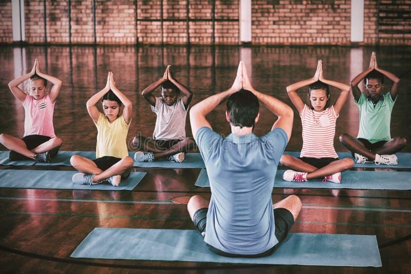 Istruisca i bambini e l'insegnante che meditano durante la classe di yoga immagini stock libere da diritti
