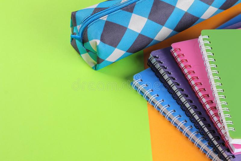 Istruisca i taccuini dei colori differenti e un astuccio per le matite su un fondo arancio e verde luminoso Rifornimenti di banco fotografie stock libere da diritti