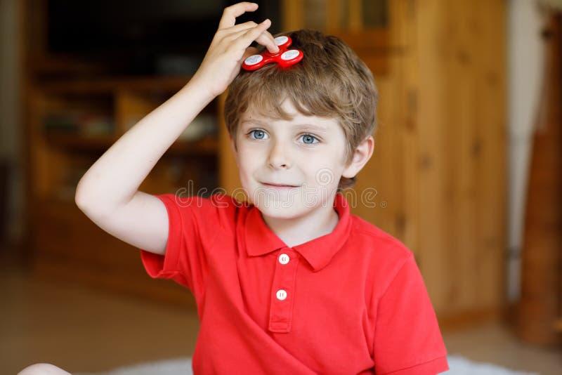 Istruisca il bambino che gioca con il tri filatore della mano di irrequietezza all'interno fotografia stock