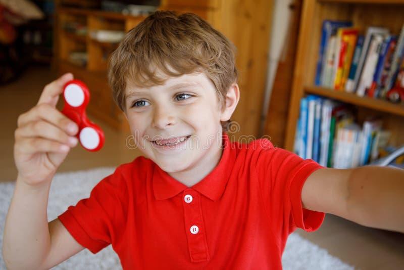 Istruisca il bambino che gioca con il tri filatore della mano di irrequietezza all'interno fotografie stock