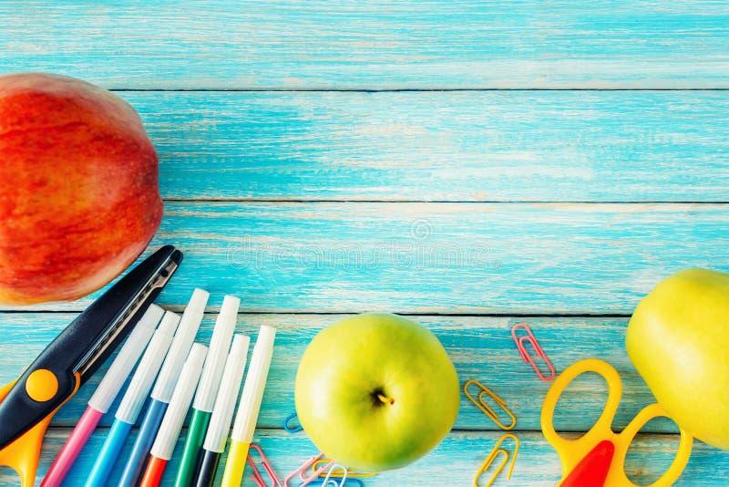Istruisca la cancelleria, gli strumenti dell'ufficio e le mele sulla vista superiore del nackground di legno blu fotografie stock
