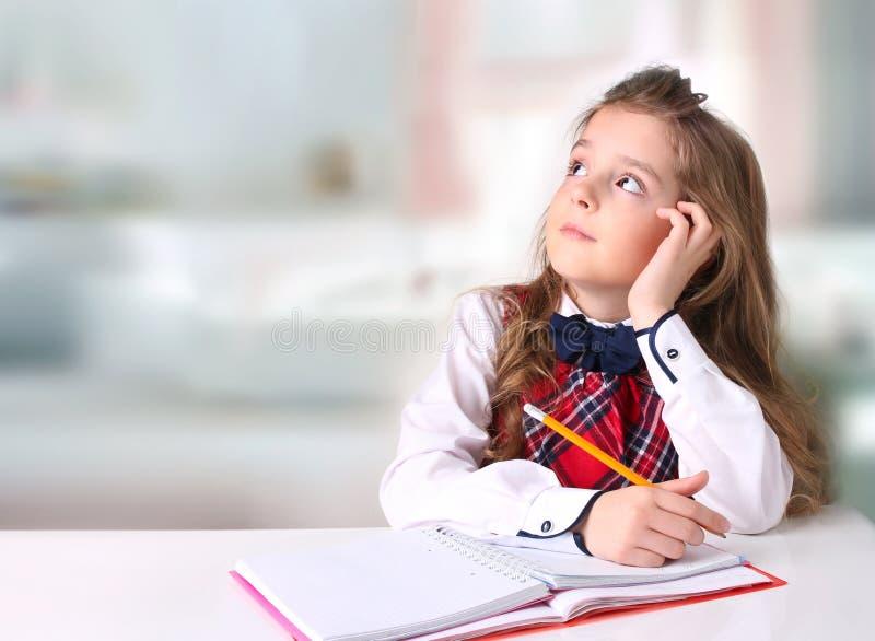 Istruisca la scrittura della ragazza al fondo vuoto dello spazio dello scrittorio immagini stock