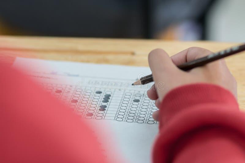 Istruisca le mani degli studenti che prendono gli esami, scriventi lo spirito della stanza dell'esame immagini stock libere da diritti