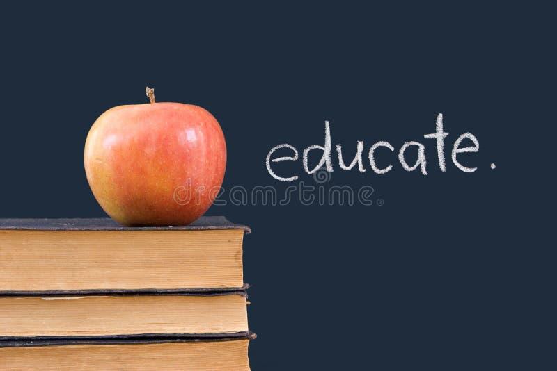 Istruisca sulla lavagna con la mela & i libri immagini stock