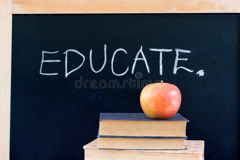 ISTRUISCA sulla lavagna con la mela & i libri immagine stock libera da diritti