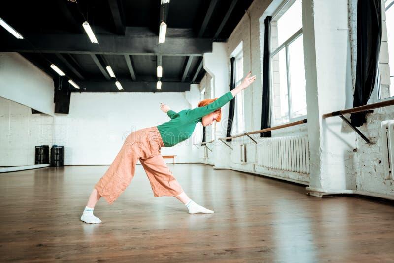 istruttore adatto Piacevole di aspetto di yoga in un collo alto verde che fa asana per allungare immagine stock