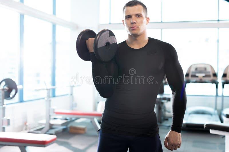 Istruttore bello Posing di forma fisica con la testa di legno in palestra immagine stock