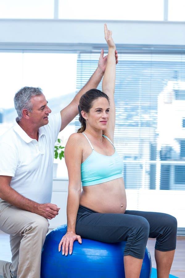 Istruttore che assiste donna incinta che si siede sulla palla immagine stock