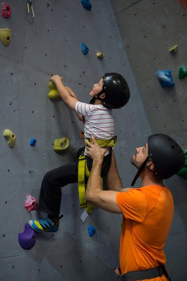 Istruttore che assiste ragazzo in arrampicata fotografie stock