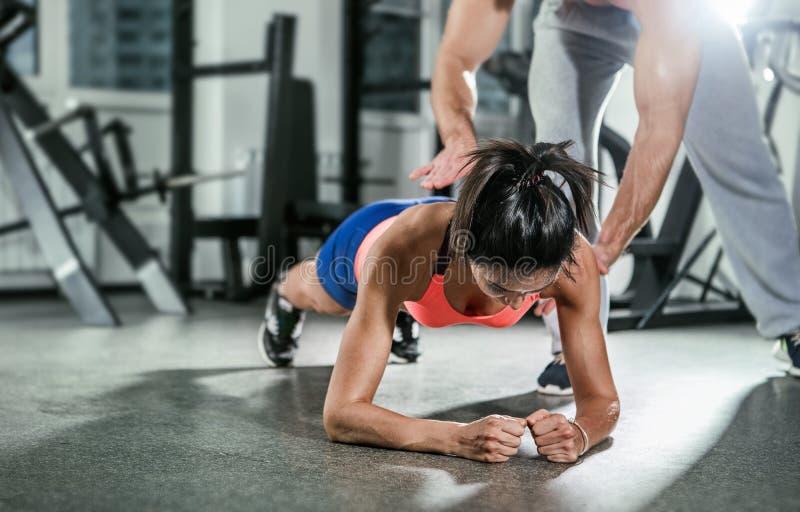Istruttore che assiste una donna muscolare su una posizione della plancia immagine stock libera da diritti
