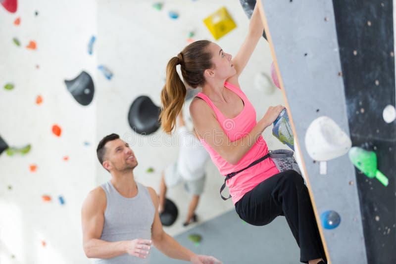 Istruttore che incoraggia la donna a salire su un muro interno immagini stock