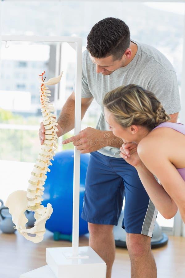 Istruttore che indica sull'osso nella spina dorsale la donna fotografia stock