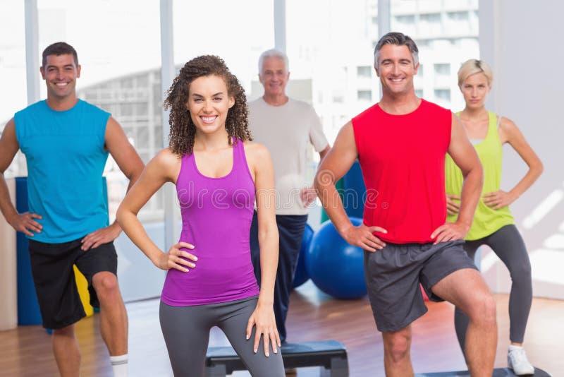 Istruttore con la classe di forma fisica che si esercita di step immagini stock