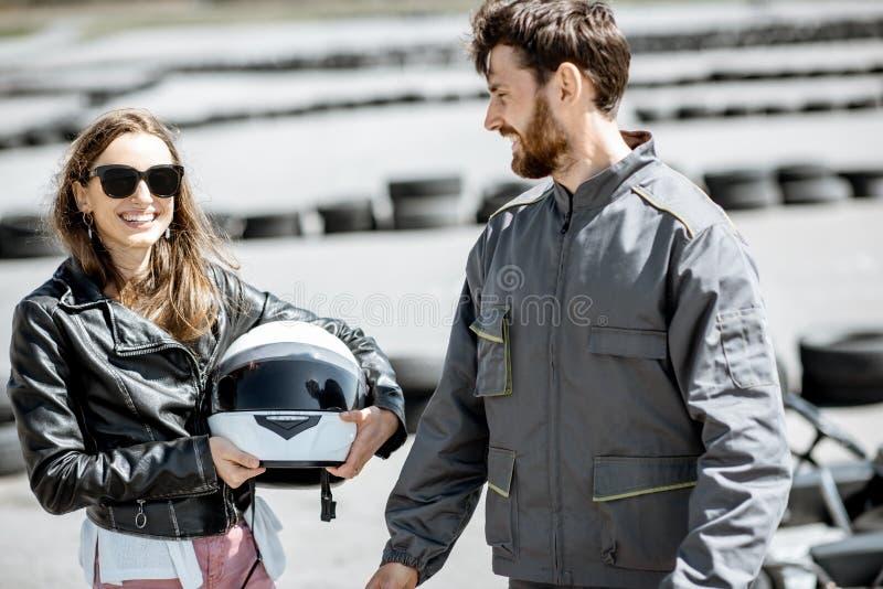 Istruttore con la donna sulla pista da go-kart fotografia stock