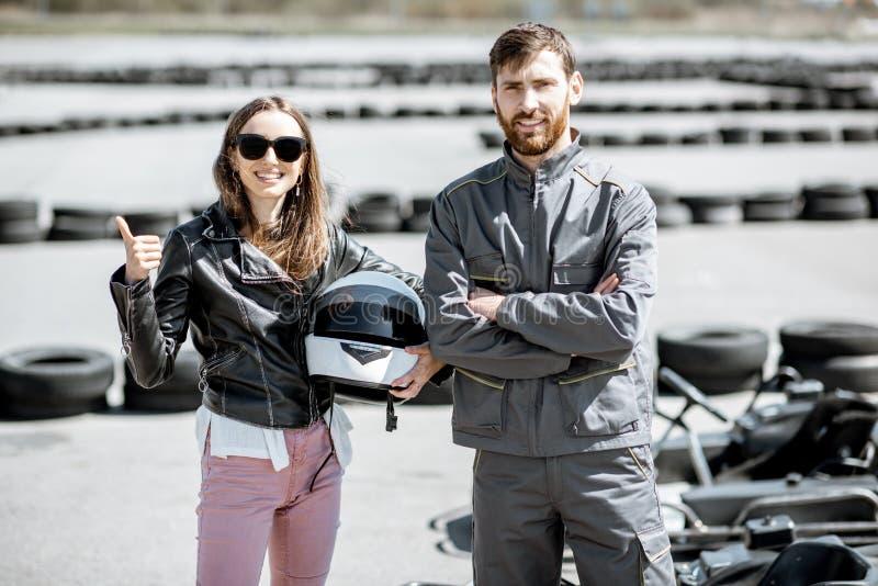Istruttore con la donna sulla pista da go-kart immagini stock libere da diritti