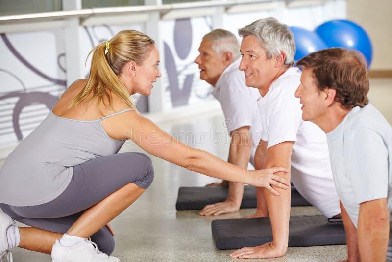 Istruttore di forma fisica che aiuta la gente senior in palestra immagini stock libere da diritti