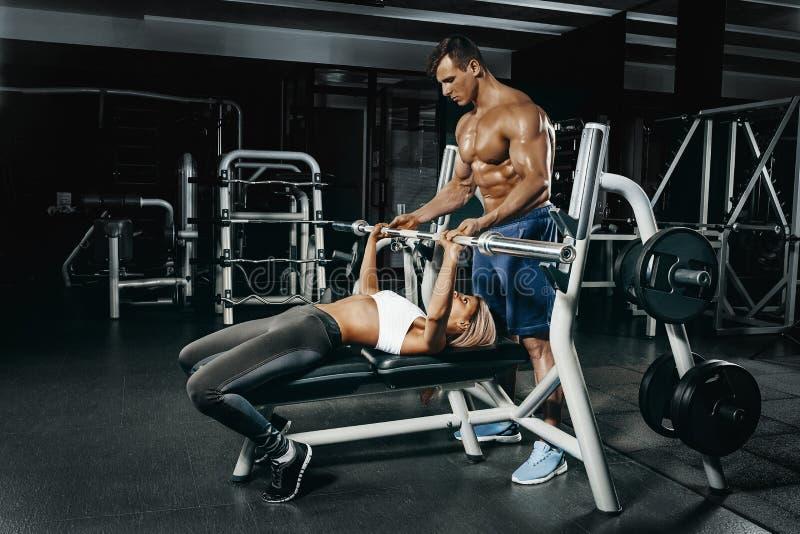 Istruttore di forma fisica che si esercita con il suo cliente alla palestra immagine stock