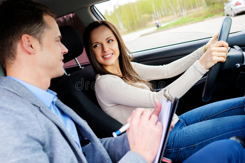 Istruttore di guida e studentessa in automobile dell'esame immagini stock