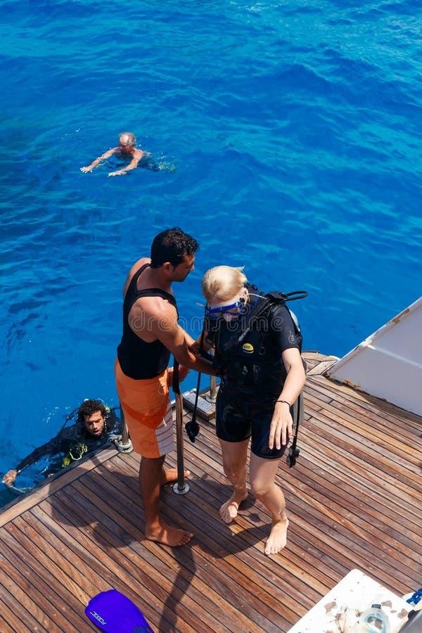Istruttore di immersione con bombole che controlla attrezzatura fotografia stock libera da diritti