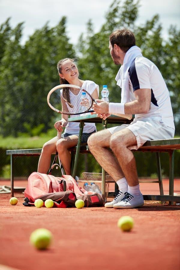 Istruttore di tennis che parla con il giocatore femminile fotografia stock