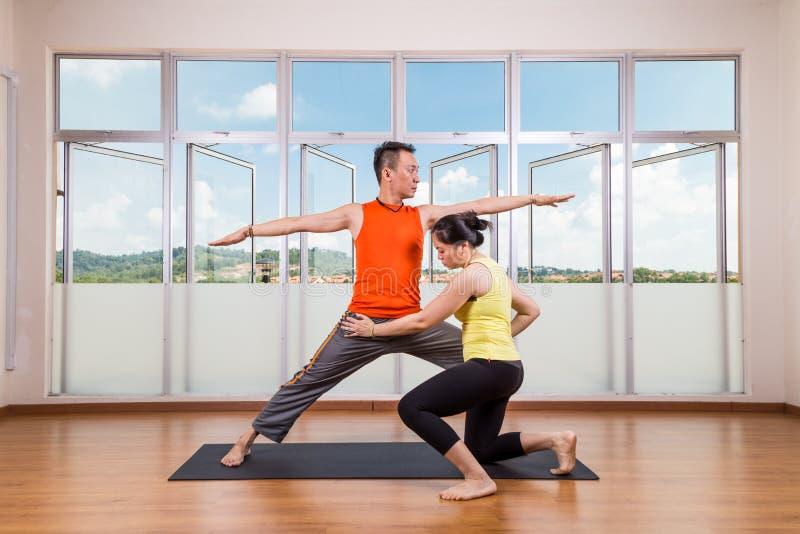 Istruttore di yoga che corregge il guerriero d'esecuzione 2 dello studente o Virab fotografie stock