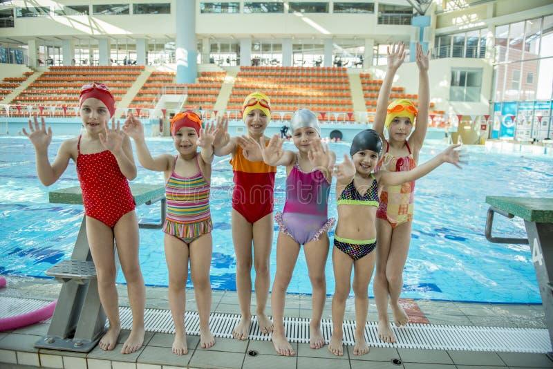 Istruttore e gruppo di bambini che fanno gli esercizi vicino ad una piscina fotografie stock