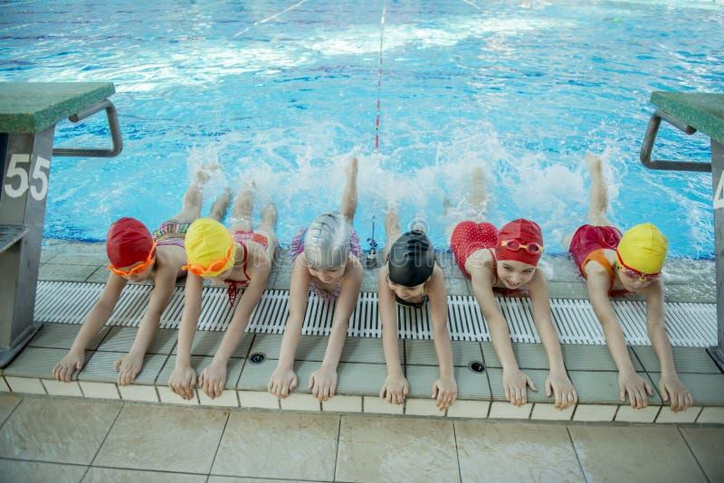 Istruttore e gruppo di bambini che fanno gli esercizi vicino ad una piscina fotografia stock libera da diritti