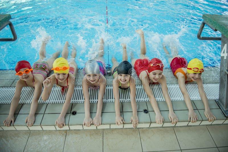 Istruttore e gruppo di bambini che fanno gli esercizi vicino ad una piscina fotografie stock libere da diritti