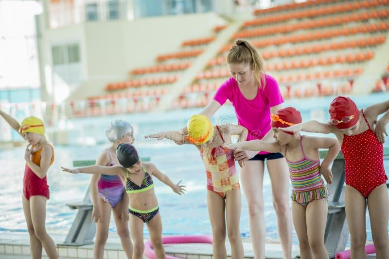 Istruttore e gruppo di bambini che fanno gli esercizi vicino ad una piscina immagini stock
