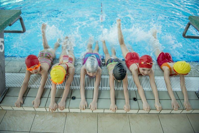 Istruttore e gruppo di bambini che fanno gli esercizi vicino ad una piscina fotografia stock
