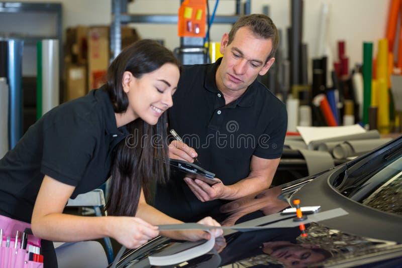 Istruttore ed apprendista in automobile che avvolge officina immagini stock libere da diritti